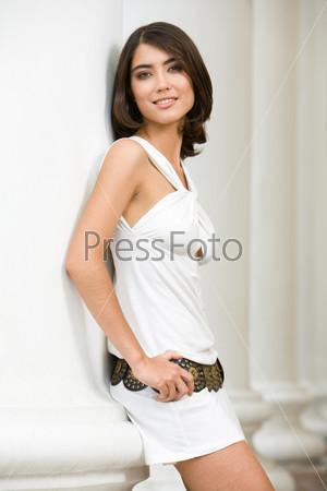 Красивая девушка в белом платье прислонилась к колонне