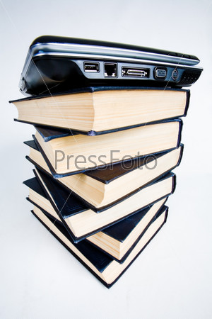Черный ноутбук лежит на высокой стопке толстых книг