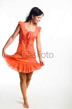 Стройная девушка в оранжевом платье танцует босиком
