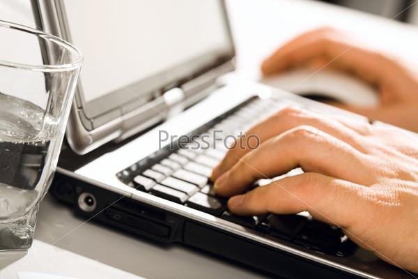 Человеческие руки рядом с ноутбуком