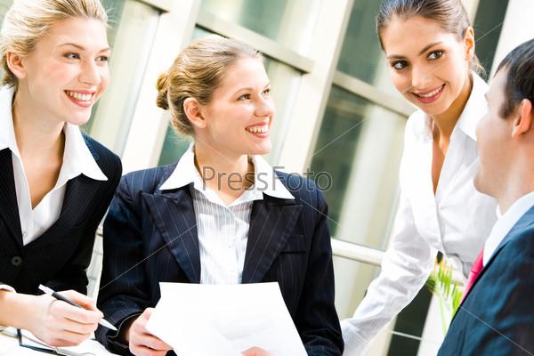 Сотрудники сидят в офисе за столом и смеются