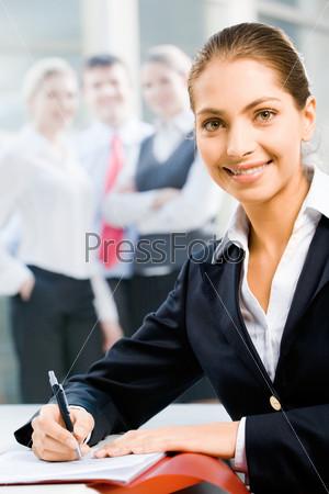Деловая женщина сидит с раскрытой папкой за столом
