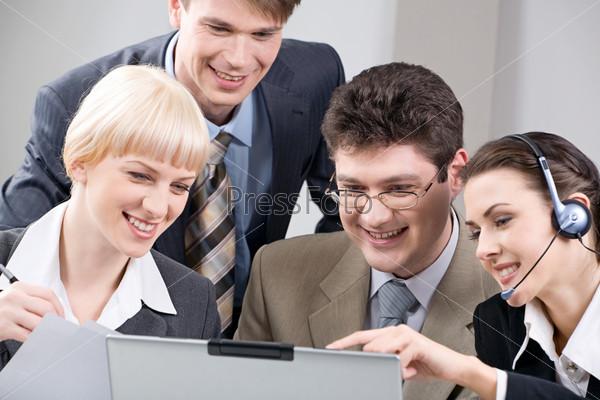 Группа сотрудников совместно изучает новый проект глядя в монитор