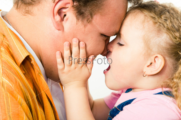 Profile of loving father with daughter touching his cheek and cuddling up to him