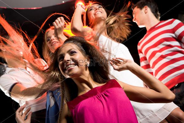 Девушка развлекается в клубе на фоне танцующих друзей