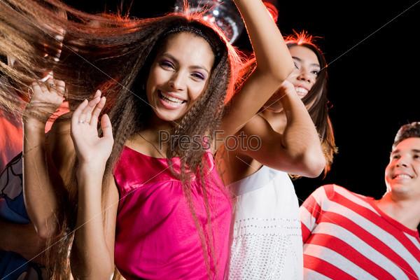Довольная девушка танцует с друзьями на вечеринке