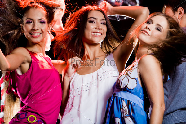 Три гламурные девушки танцуют на дискотеке в ночном клубе