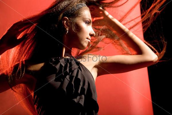 Восхитительная девушка в черном платье танцует на красном фоне