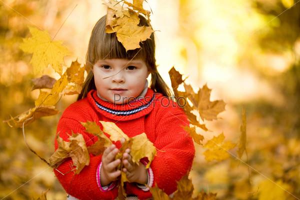 Очаровательная девочка на фоне осенних листьев