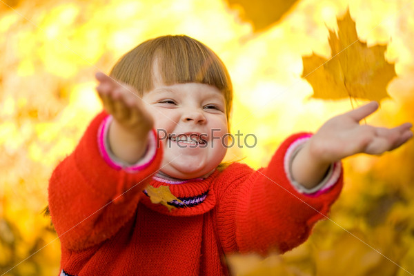 Лицо счастливого ребенка кидающего осенние листья