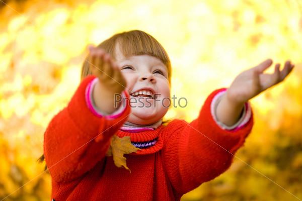 Радостная девочка подбрасывает вверх желтые листья