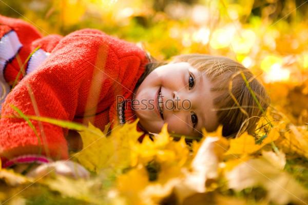 Фотография на тему Хорошенькая девочка лежит на поляне, покрытой осенней листвой