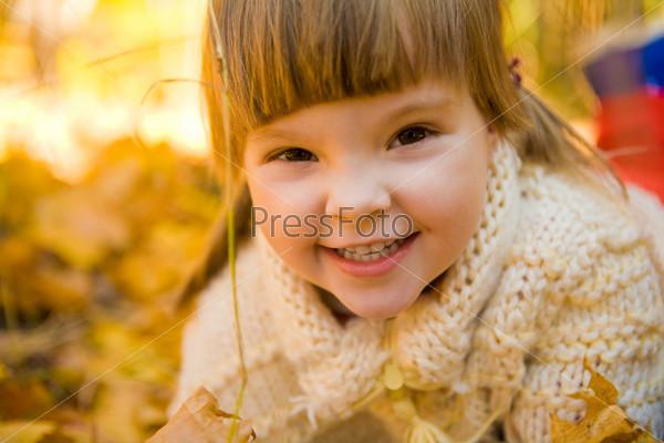 Очаровательный ребенок среди ярких осенних листьев
