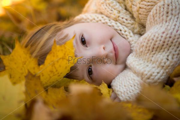 Задумчивая девочка лежит на осенних листьях