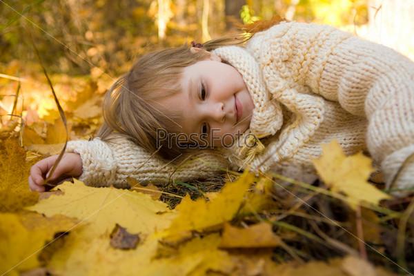 Маленькая девочка мечтает, лежа на осенних листьях