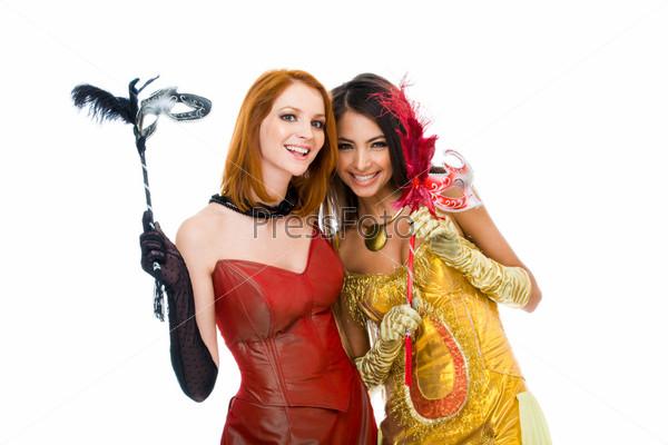 Две девушки секретничают держа в руках карнавальные маски