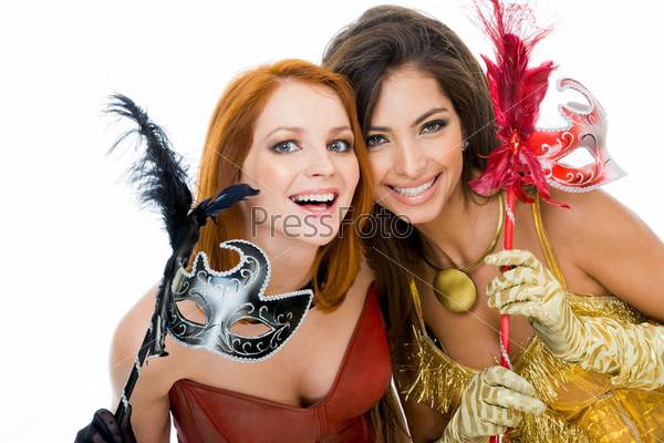 Две таинственные девушки игриво смотрят в камеру с масками в руках