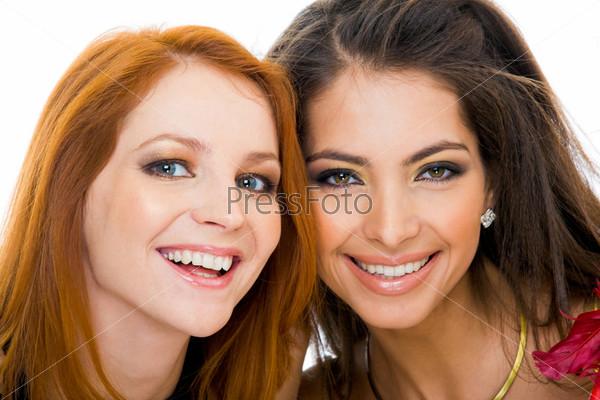 Две красивые девушки крупным планом смотрят в камеру с улыбками