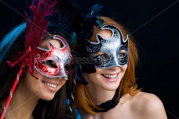Две красивые девушки в карнавальных масках на черном фоне