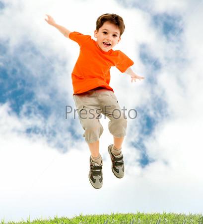 Мальчик в оранжевой футболке подпрыгивает раскинув руки в стороны
