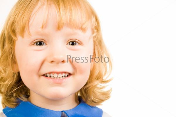 Красивая рыжая девочка с улыбкой смотрит в камеру