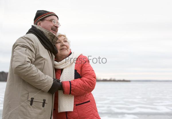 Пожилая пара в зимней одежде на фоне природы