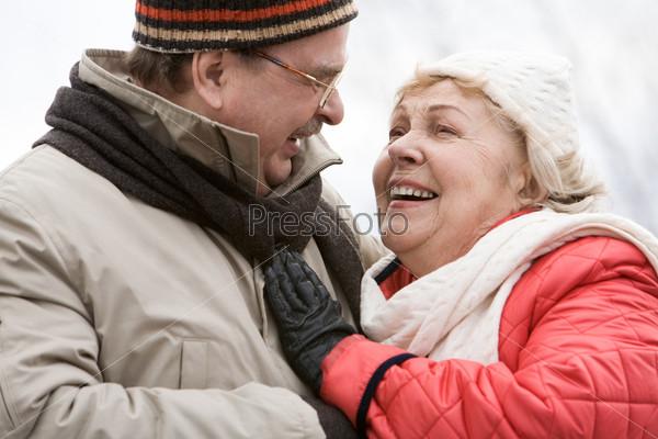 Счастливая пожилая пара стоит обнявшись и смеется