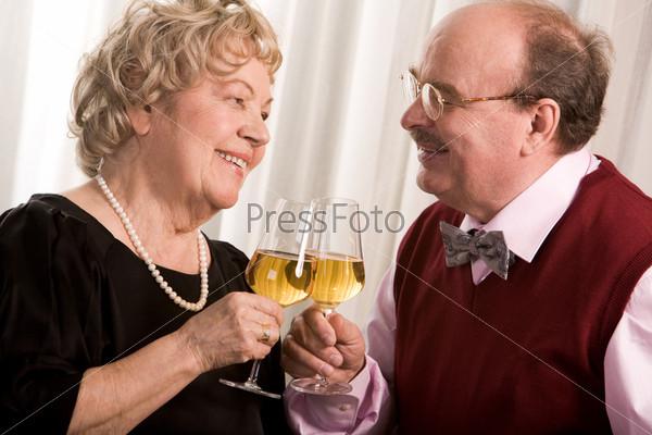 Пожилая пара отмечает событие в семье держа бокалы