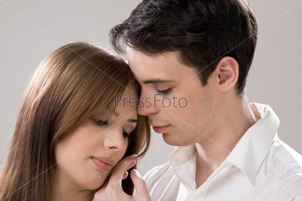 Молодой человек нежно прикасается к щеке своей подруги