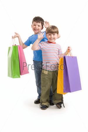 Фотография на тему Два улыбающихся мальчика держат разноцветные пакета для покупок на белом фоне