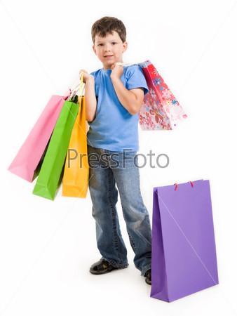 Радостный мальчик держит в руках подарочные пакеты