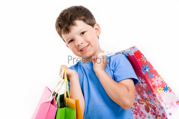 Фотография на тему Мальчик с разноцветными пакетами в руках улыбается на белом фоне