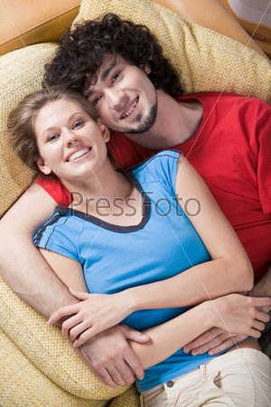 Влюбленная пара лежит обнявшись на диване и улыбается