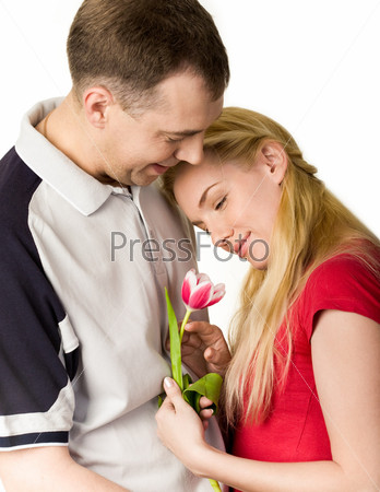 Девушка с тюльпаном в руке прислонилась к плечу молодого человека