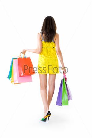 Симпатичная девушка в желтом сарафане стоит спиной и держит в руках пакеты с покупками