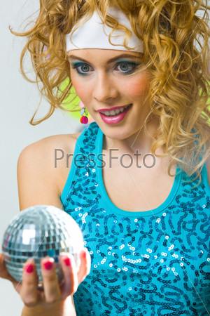 Красивая девушка удивленно смотрит на блестящий шар