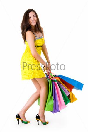 Гламурная кокетка в стильном сарафане держит в руках тяжелые пакеты с покупками