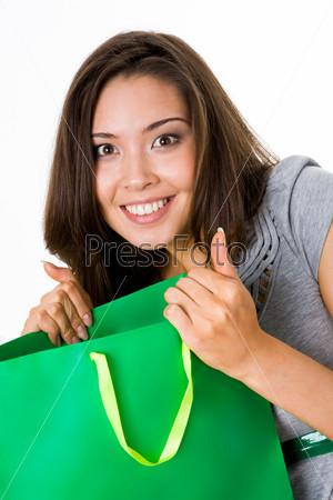 Удивленная девушка держит зеленый пакет и смотрит в камеру широко раскрытыми глазами
