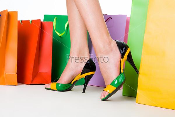 Женские ножки в стильных туфлях проходят мимо разноцветных пакетов