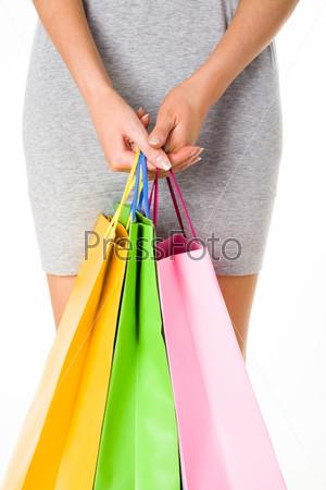 Девушка в сером платье держит в руках пакеты с покупками