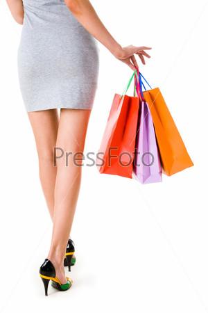 Элегантная девушка аккуратно держит несколько разноцветных пакетов с покупками на белом фоне