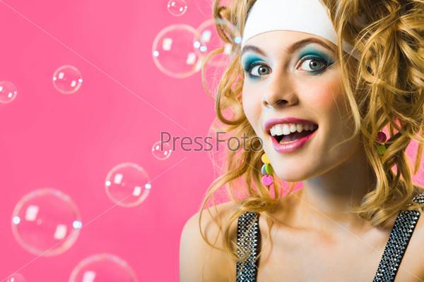 Эмоциональная девушка с восторгом смотрит в камеру в окружении мыльных пузырей