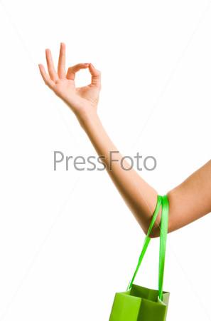 Разноцветные пакеты на руке, показывающей знак О`кей