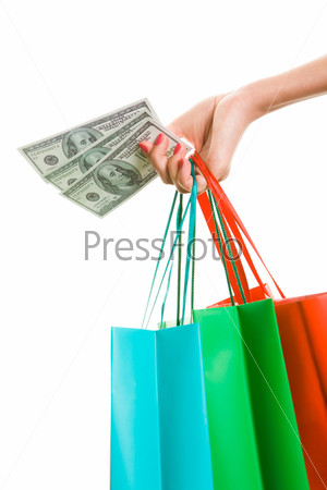 Женская рука с разноцветными пакетами расплачивается долларовыми купюрами