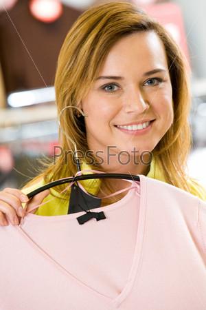 Симпатичная девушка в торговом центре показывает новую кофточку