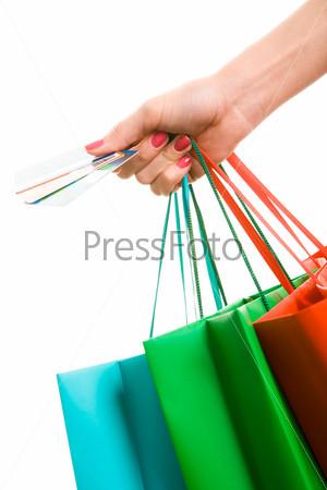Женская рука с разноцветными пакетами расплачивается кредитными карточками
