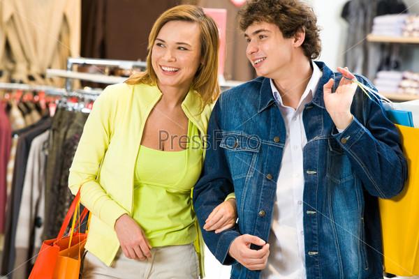 Счастливый молодой человек с девушкой несет разноцветные пакеты с покупками в торговом центре