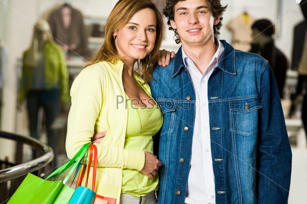 Влюбленная пара стоит в торговом центре и улыбается