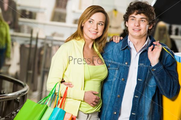Влюбленная пара выбирают одежду в торговом центре