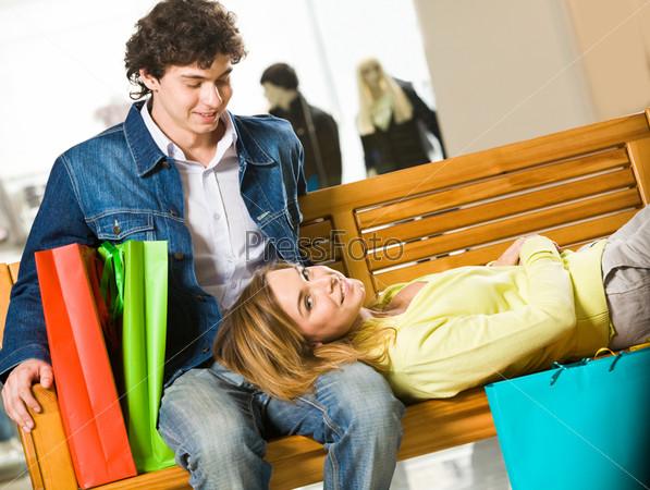 Девушка устала после шоппинга и прилегла на колени своего молодого человека